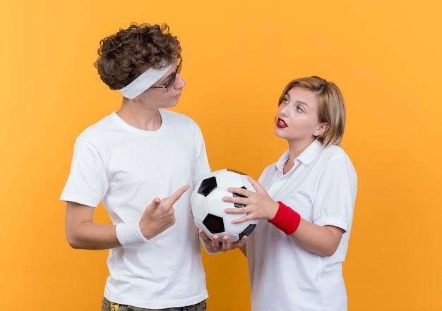 Giovane coppia sportiva uomo serio tenendo il pallone da calcio guardando la sua ragazza sorridente in piedi sopra la parete arancione