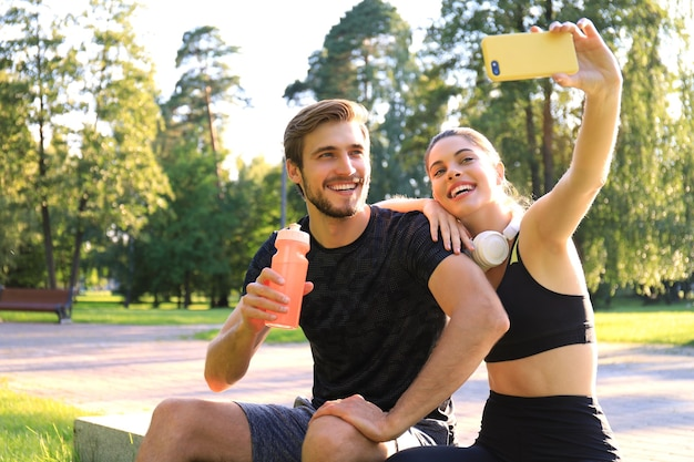 Young sporty couple in sportswear sitting on parapet in urban park and taking selfie after workout on summer sunny day.