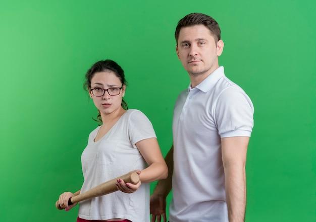 緑の壁の上に立っている深刻な顔を持つ彼女のボーイフレンドの隣に立っている野球のバットを持つ若いスポーティなカップルの女性