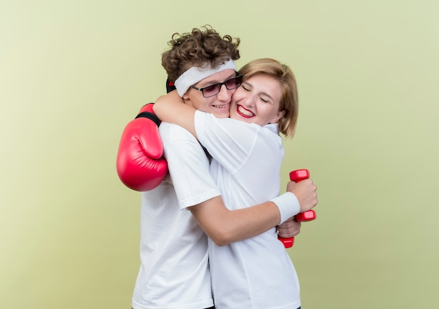 Giovane donna sportiva delle coppie con i guantoni da boxe che abbraccia il suo ragazzo con i guantoni da boxe felice e positivo in piedi sopra la parete chiara