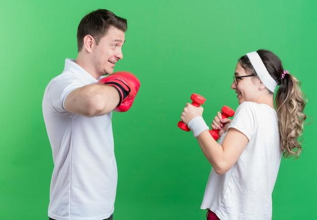 녹색 벽 위에 유쾌하게 서있는 권투 장갑과 그녀의 남자 친구를보고 아령 젊은 스포티 한 부부 여자