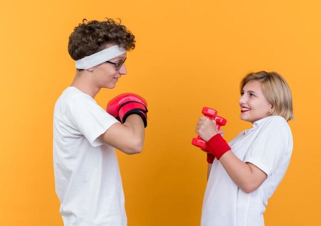 오렌지 벽 위에 유쾌하게 서있는 권투 장갑과 그녀의 남자 친구를보고 아령 젊은 스포티 한 부부 여자