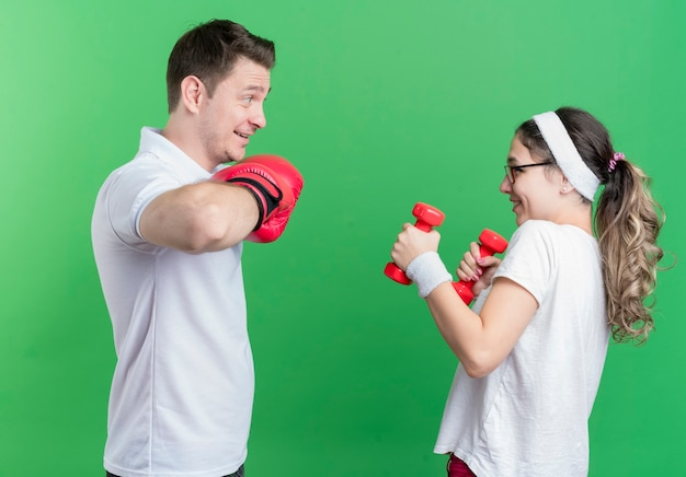 Young sporty couple woman with dumbbells looking at her boyfriend with boxing gloves smiling cheerfully standing over green wall