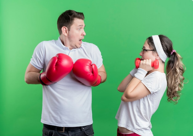 Young sporty couple woman with dumbbells looking at her boyfriend with boxing gloves surprised and confused standing over green wall