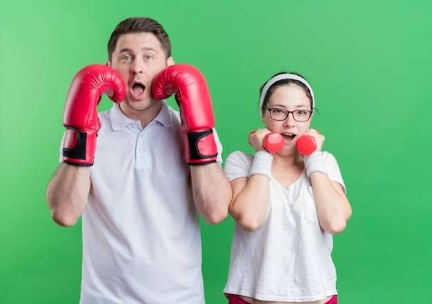 Young sporty couple woman with dumbbells standing next to her boyfriend with boxing gloves posing  surprised and confused standing over green wall
