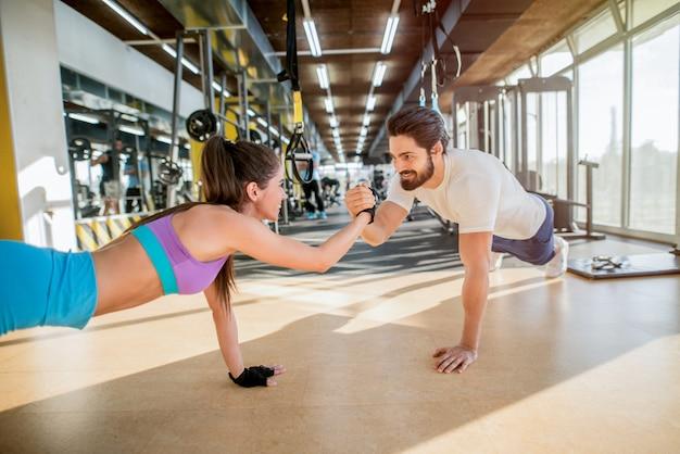 Молодая спортивная пара вместе работает в тренажерном зале. выполнение упражнений планки, удерживая друг друга за одну руку.