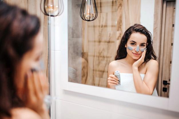 Молодая спортивная темноволосая красивая женщина делает утреннюю рутину в зеркало. она посмотрела в зеркало и надела маску на лицо.