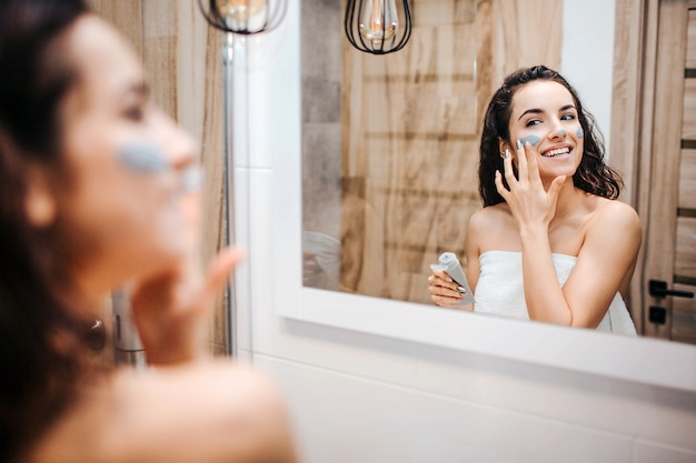 Young sporty dark-haired beautiful woman doing morning or evening routine at mirror. cheerful happy model wrapped in white towel and put mask on face.