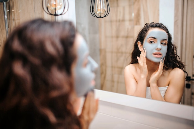 Young sporty dark-haired beautiful woman doing morning evening routine at mirror. she has cream mask on face and touch it with hands. calm and peaceful.