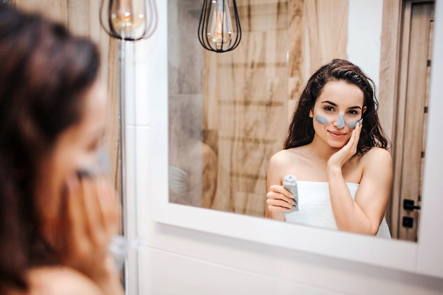 Young sporty dark-haired beautiful woman doing morning evening routine at mirror. she look in mirror and put some mask on face.