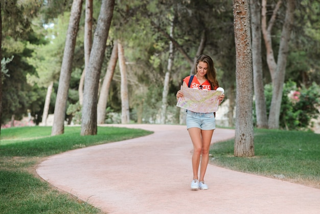 Young sporty female traveler with cute smile studying a map in park