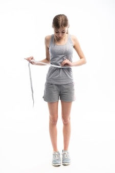 Young, sporty, fit and beautiful girl with the measuring tape over white.