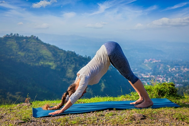 Young sporty fit woman doing yoga oudoors in mountains