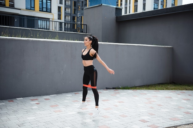 Young sporty fit woman with long ponytail in sportswear squats with fitness elastic band on legs outdoors. sports concept, healthy lifestyle
