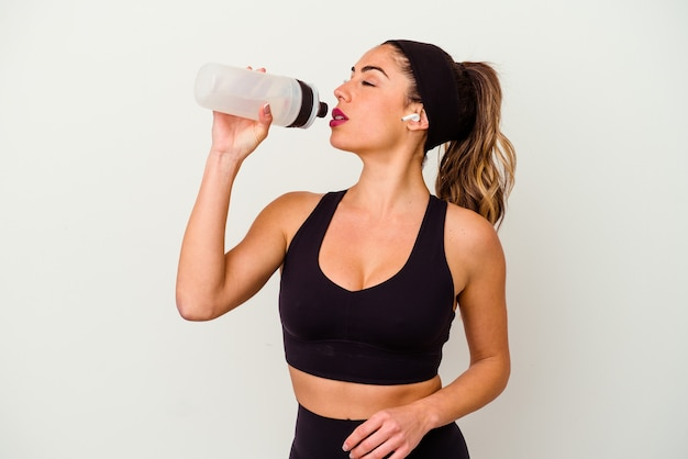 Young sporty fitness woman drinking water from bottle isolated on white background