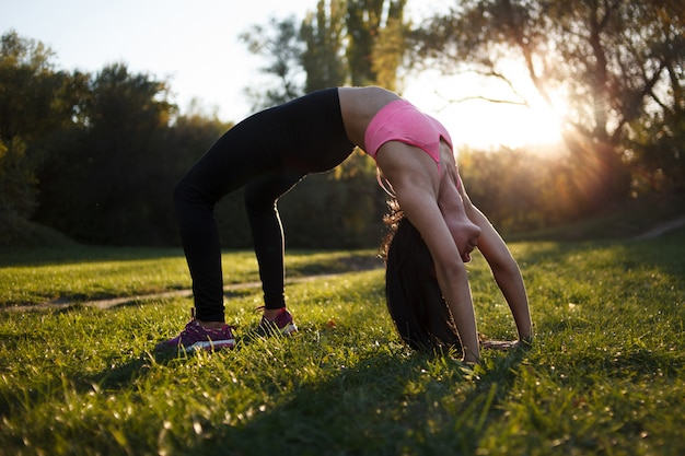 Young sporty girl doing yoga in the park