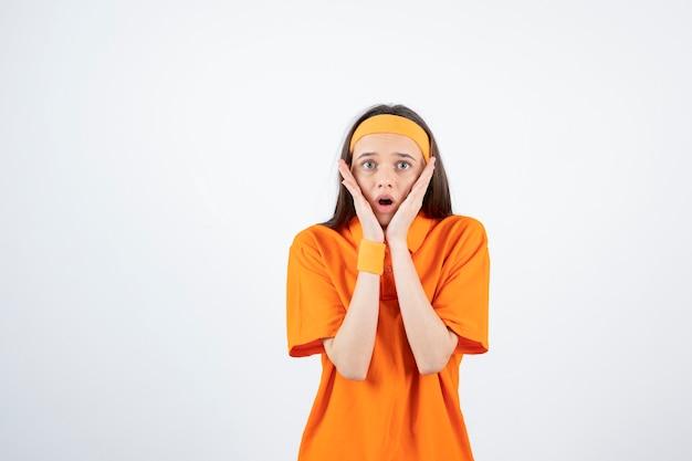 白の上に立っているオレンジ色の衣装で若いスポーティな女の子。