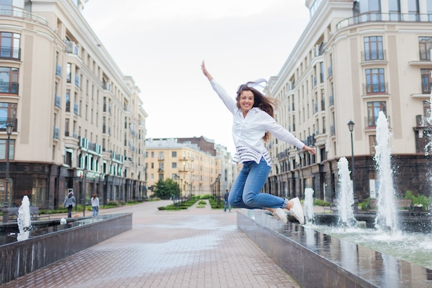 Young sporty girl jumping for joy at the fountain.