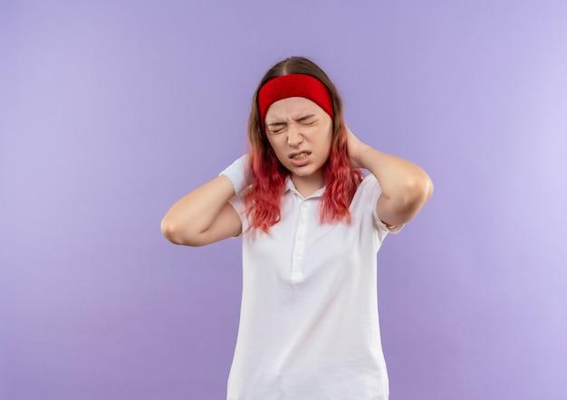 Giovane ragazza sportiva in cerca di malessere toccando il suo collo sensazione di dolore in piedi sopra la parete viola