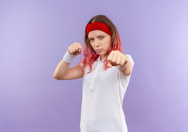 Giovane ragazza sportiva in posa come un pugile con i pugni chiusi in piedi sopra il muro viola