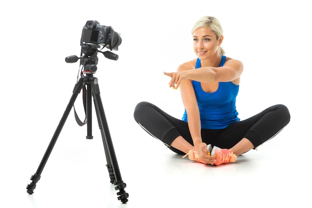 The young sporty girl with a fair hair in a black sports topic, black leggings and bright sneakers does an extension of muscles in front of the camera.