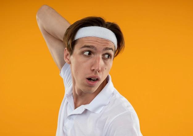 Giovane ragazzo sportivo guardando al lato che indossa la fascia e il braccialetto mettendo la mano sul collo isolato sulla parete arancione