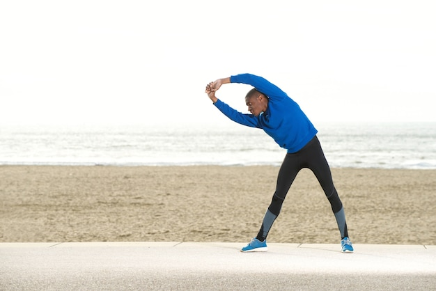 Young sporty guy stretching exercise at the beach