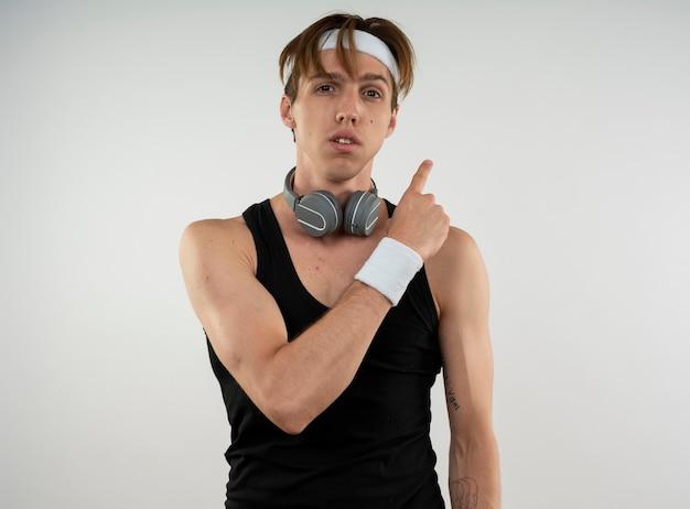 コピースペースのある白い壁に隔離された後ろの首のポイントにヘッドフォンでヘッドバンドとリストバンドを身に着けている若いスポーティな男
