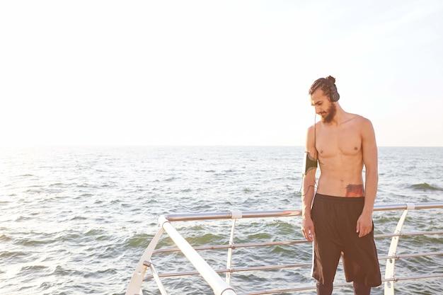あごひげを生やした若いスポーティな男、朝の海辺でのジョギングの後に休憩し、ヘッドフォンでお気に入りのミックスを聴きます。
