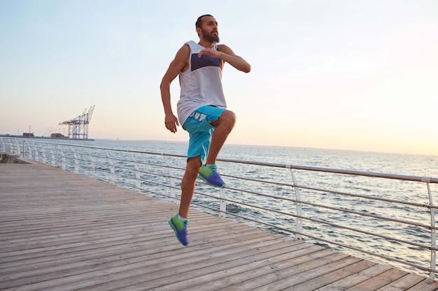Giovane ragazzo sportivo bello con la barba che salta facendo esercizi mattutini in riva al mare, riscaldamento prima di correre.