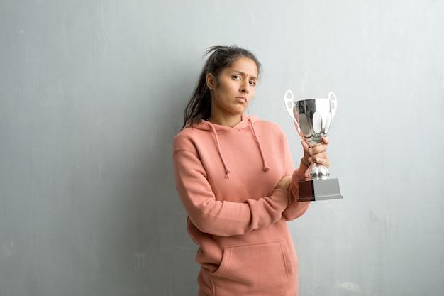 非常に怒っていると動揺の壁に対してスポーティな若いインド人女性
