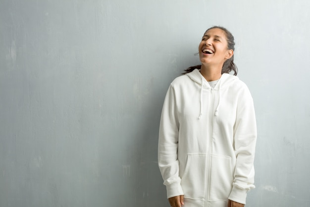 Young sporty indian woman against a gym wall laughing and having fun, being relaxed and cheerful, feels confident and successful