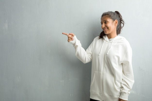 Young sporty indian woman against a gym wall pointing to the side
