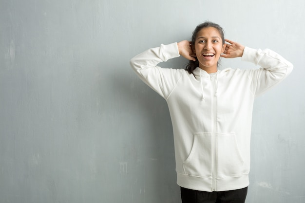 Young sporty indian woman against a gym wall surprised and shocked, looking with wide eyes