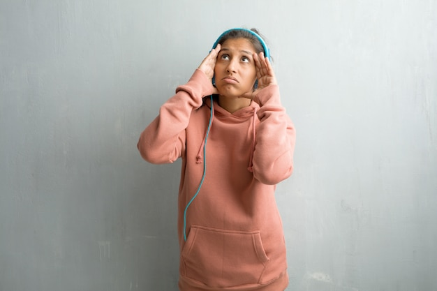 Young sporty indian woman against a wall frustrated and desperate, angry and sad with hands on head. listening music with headphones.