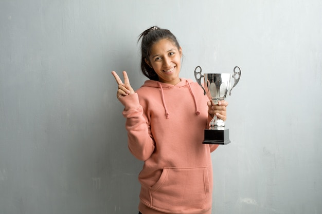 Young sporty indian woman against a wall fun and happy, positive and natural, doing a gesture of victory, peace concept. holding a trophy.