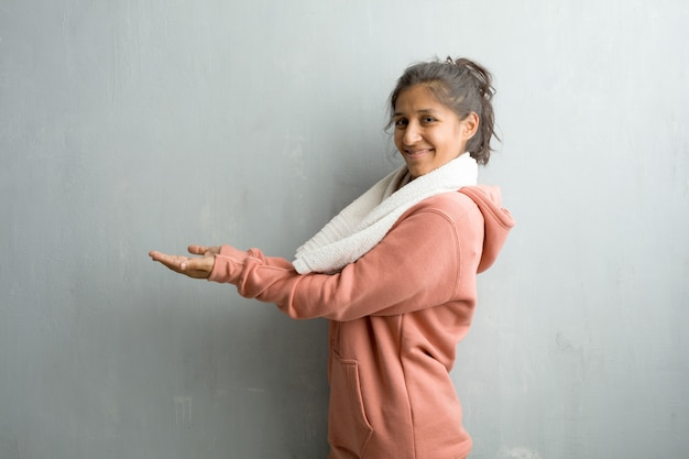 Young sporty indian woman against a wall holding something with hands