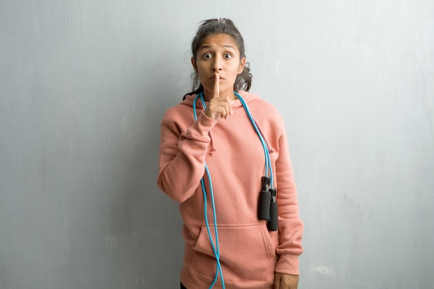 Young sporty indian woman against a wall keeping a secret or asking for silence, serious face.