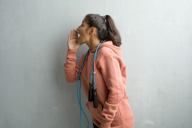 Young sporty indian woman against a wall screaming angry, expression of madness and mental instability