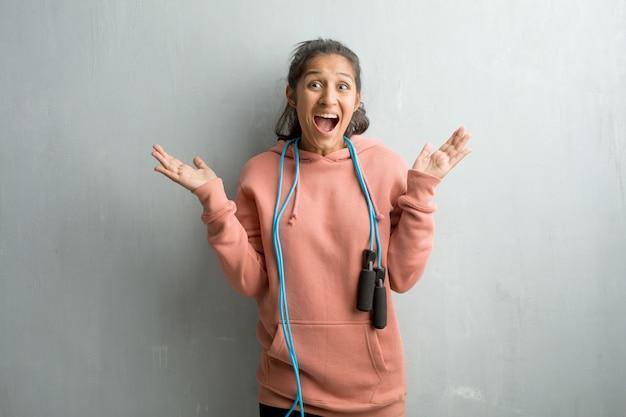 Young sporty indian woman against a wall screaming happy, surprised by an offer or a promo