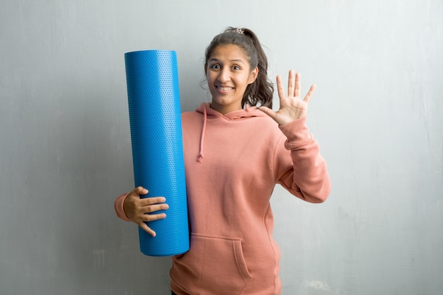 Young sporty indian woman against a wall showing number five