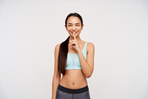 若いスポーティーな女性、暗い長い髪のかなりアジアの女性がポニーテールに集まった。スポーツウェアを着て、沈黙のサインを見せて、笑っている。白い背景の上に分離されたカメラで見て