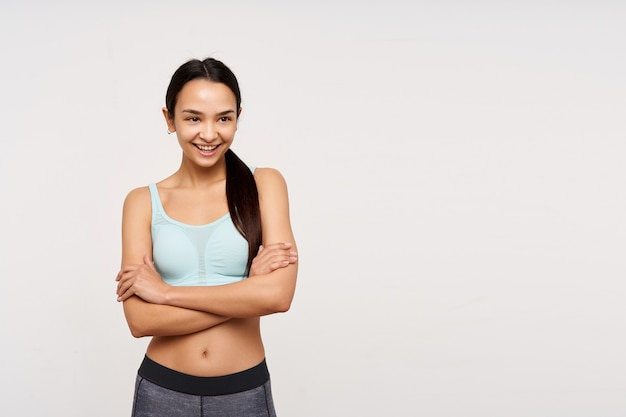 若いスポーティーな女性、暗い長い髪のかなりアジアの女性。スポーツウェアを着て、胸に腕を組んで笑っている。白い背景の上に分離されたコピースペースで右を見て