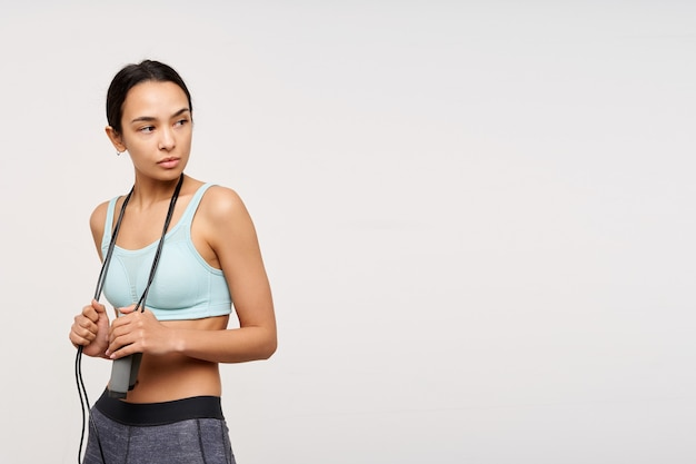 Young sporty lady, serious asian woman with dark long hair. wearing sportswear and holding a jump rope over her neck. watching to the right at copy space, isolated over white background