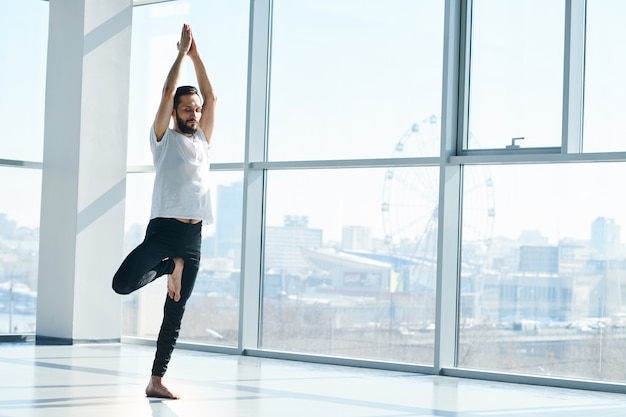 Young sporty man in activewear keeping balance while practicing one of yoga exercises during workout