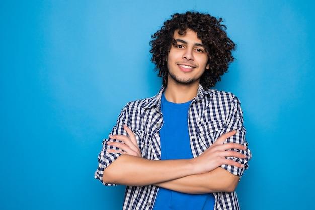 Молодой спортивный человек недовольно хмурится, скрестив руки на синей стене