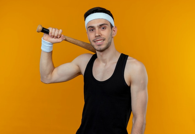 Young sporty man in headband holding basebal bat  smiling confident standing over orange wall