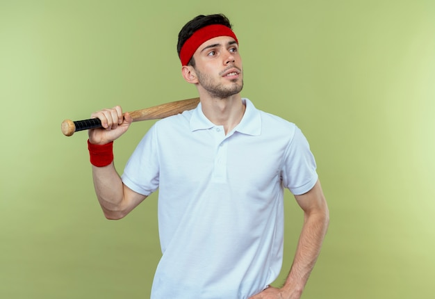 Young sporty man in headband holding baseball bat looking aside with pensive expression standing over green wall