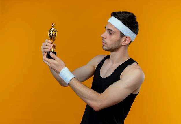 Young sporty man in headband holding his trophy looking at it with confident serious expression standing over orange wall