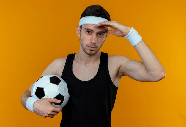 Young sporty man in headband holding soccer ball  with hand over head with serious face standing over orange wall